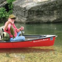 Angler in canoe with a nice limestone stream smallmouth bass