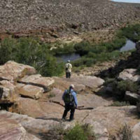 Two anglers hiking ino a river canyon in South Africa