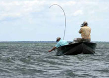 Two anglers in a boat on on a windy lake with rough waves
