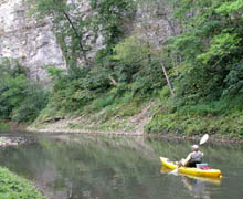 A river kayak angler in front of limestone bluffs