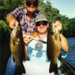 An angler and his father in the boat, each holding a big smallmouth bass.