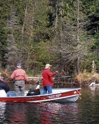 Two guests and a guide fishing on a portage-over lake.