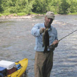 Tim Holschlag wade fishing beside his kayak, holding a big smallie